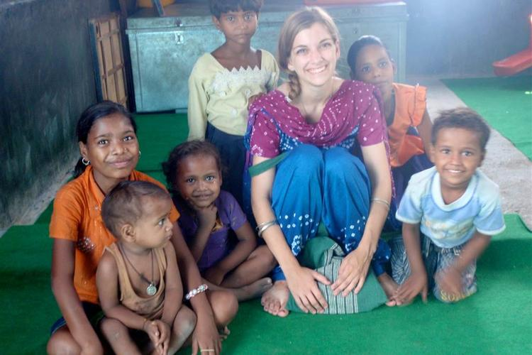 Shaina Watrous sitting with children in India
