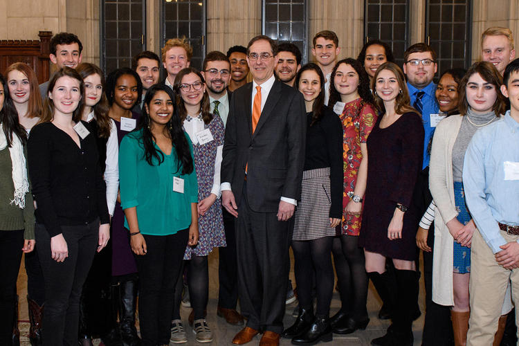 University President Christopher Eisgruber standing with students for a group photo