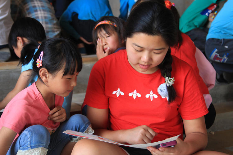 Internship student reading to a child in Macha village