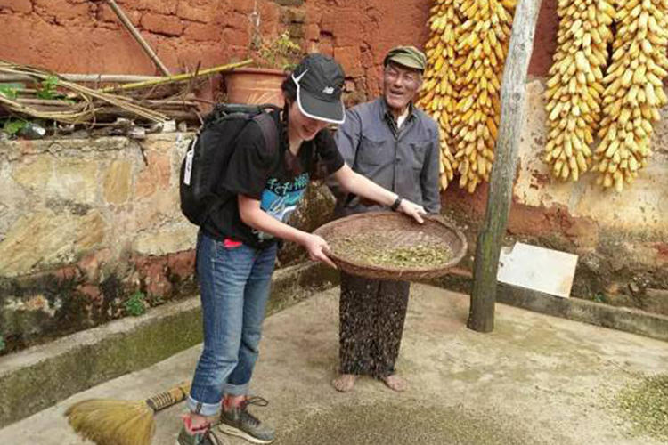 Kisara Moore sifting buckwheat in Kunming, China next to an elderly Chinese man