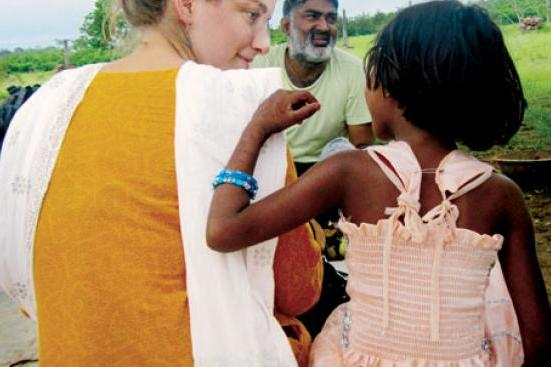 Shaina Watrous '14, director of a documentary about Ajeet Singh, center, listens to a child in Varanasi, India.