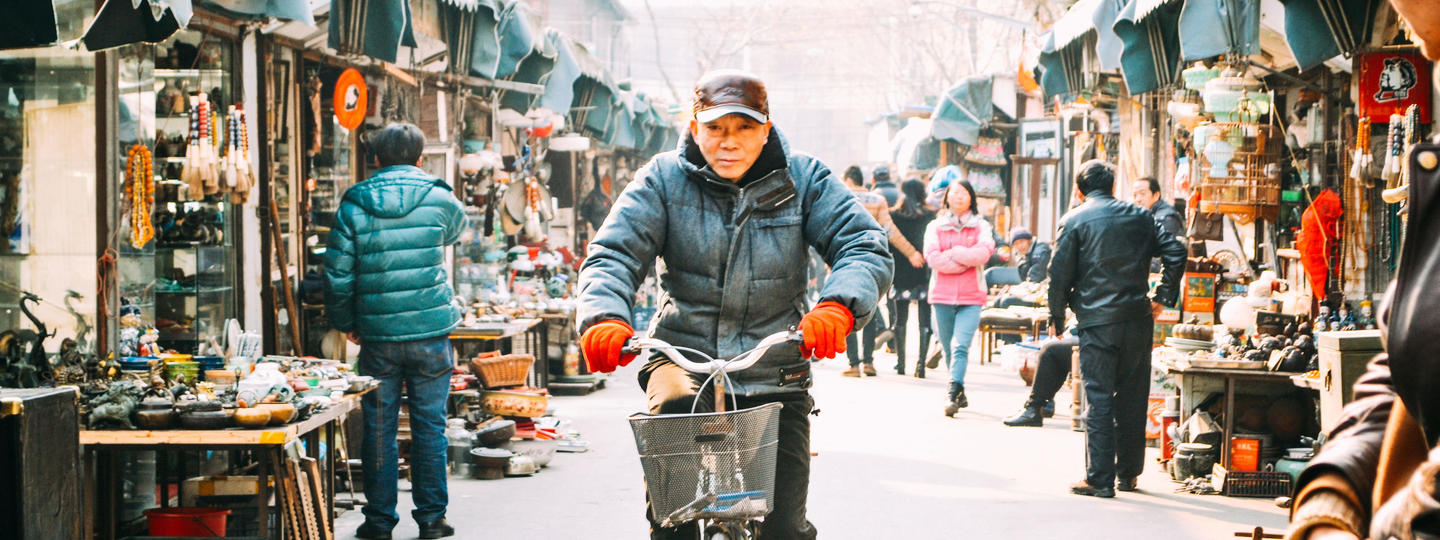 Man riding a bike down a street in China