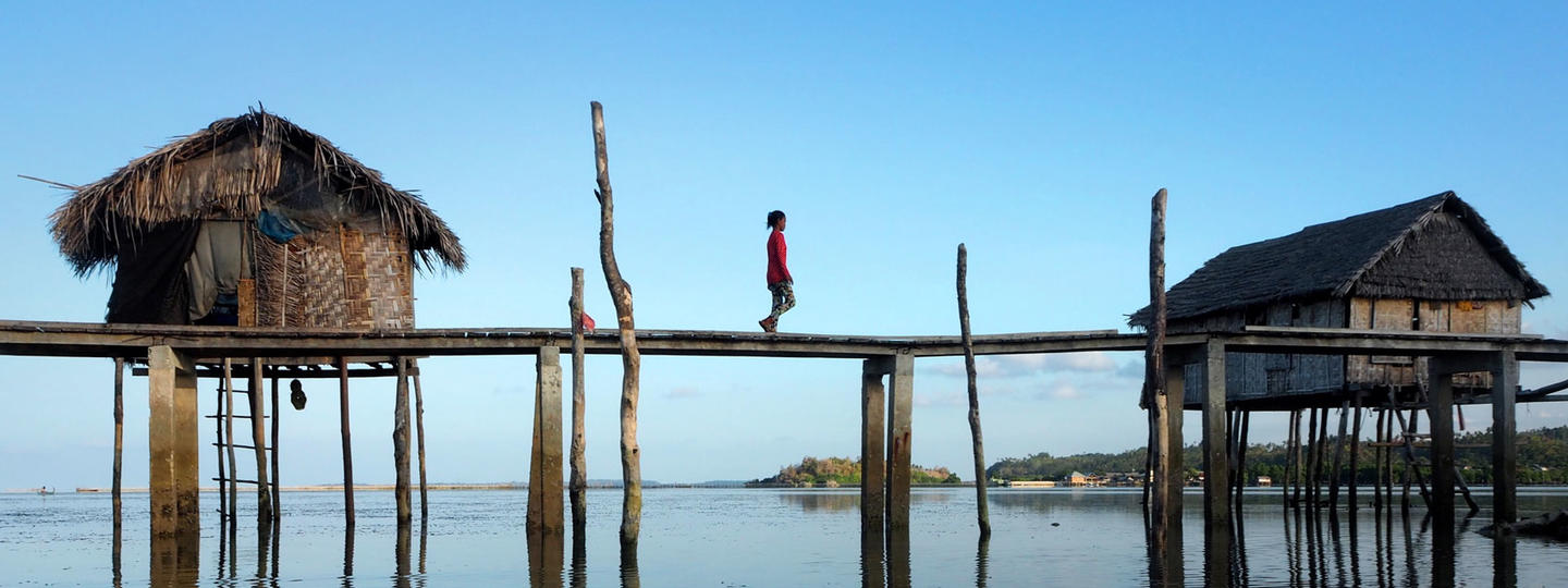 Person walking on bridge between two huts