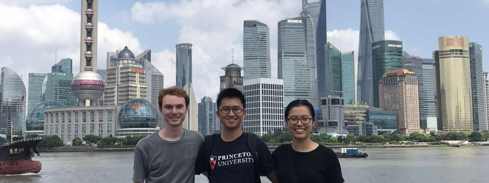 students posing for a picture with a Chinese city in the background