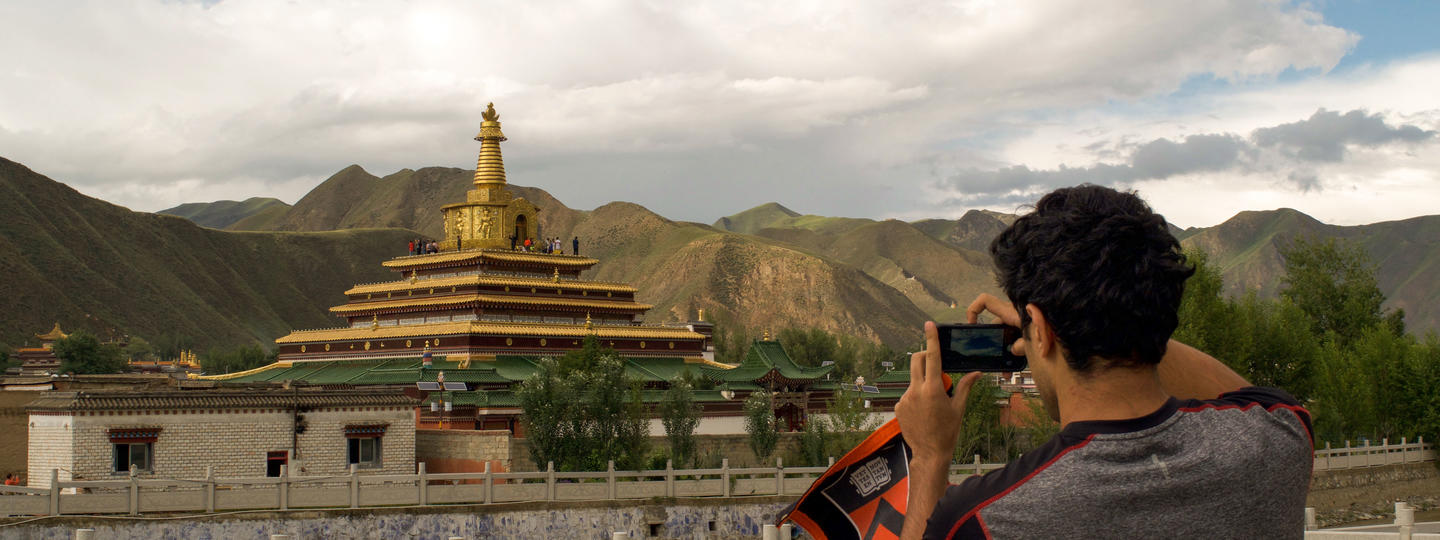 Student taking a photo of a building in China