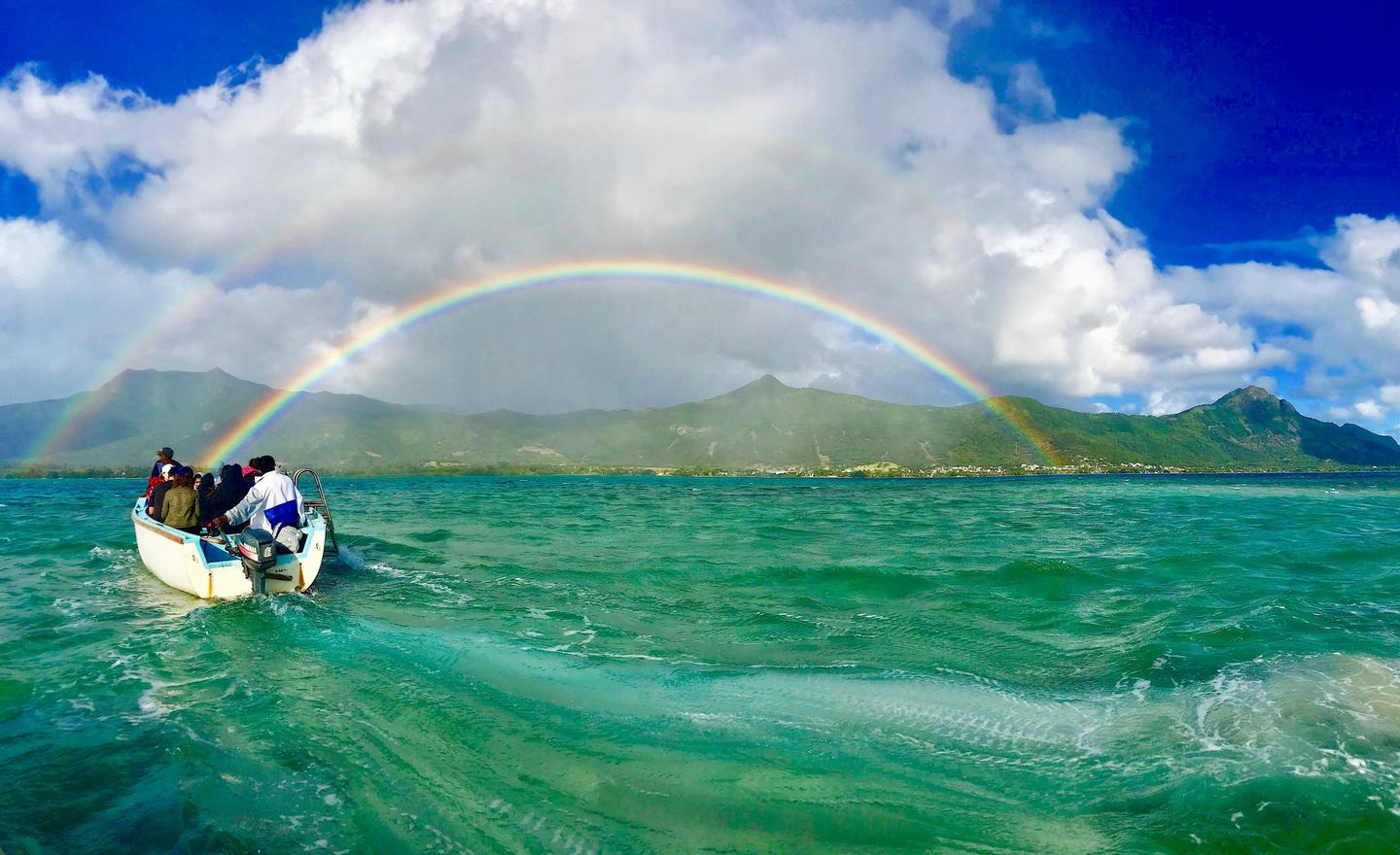 A boat in the ocean with a rainbow in the background