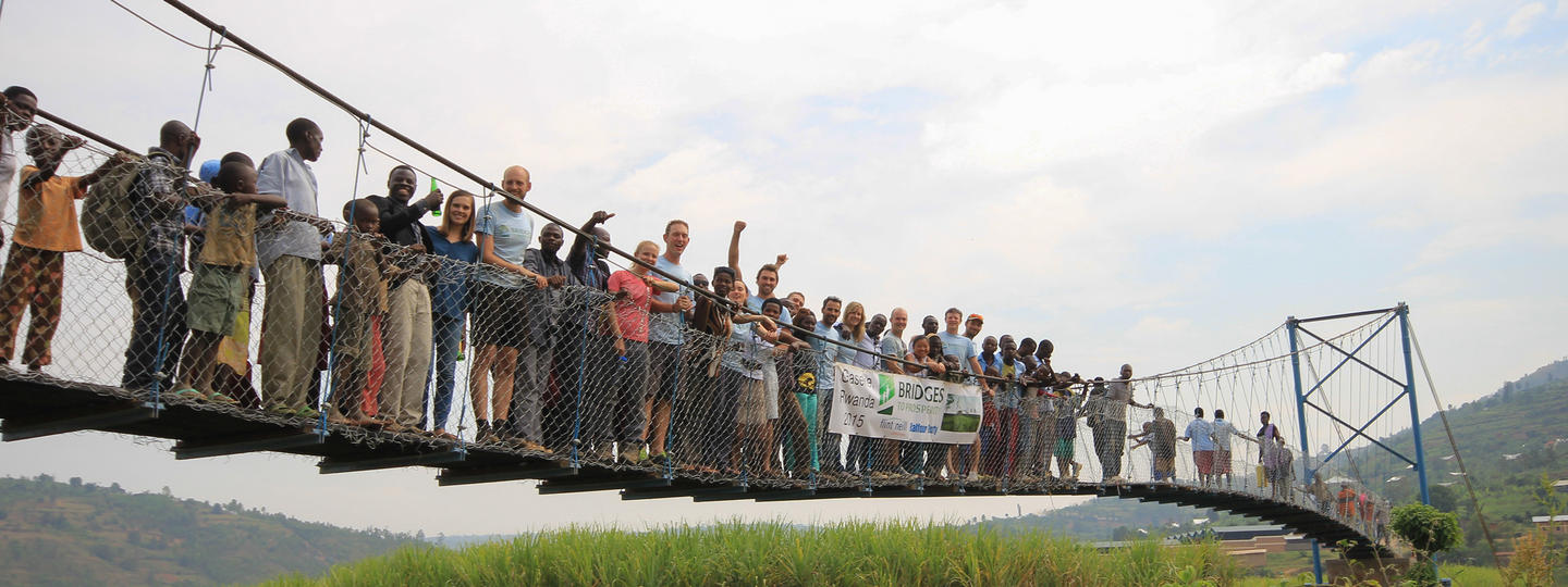 a line of people standing on a bridge