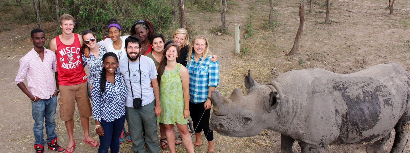 Students standing together next to a rhino