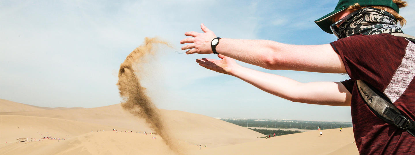 A person in China tossing sand in the dessert