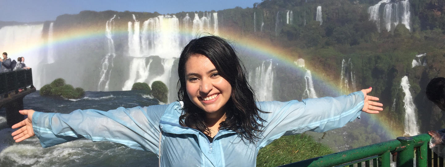 Woman standing in front of a waterfall in front of a rainbow
