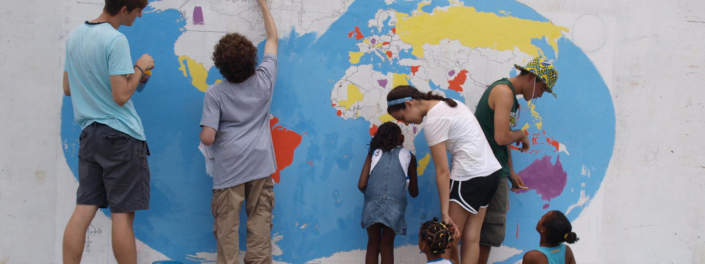Bridge year students painting a mural with children in Brazil