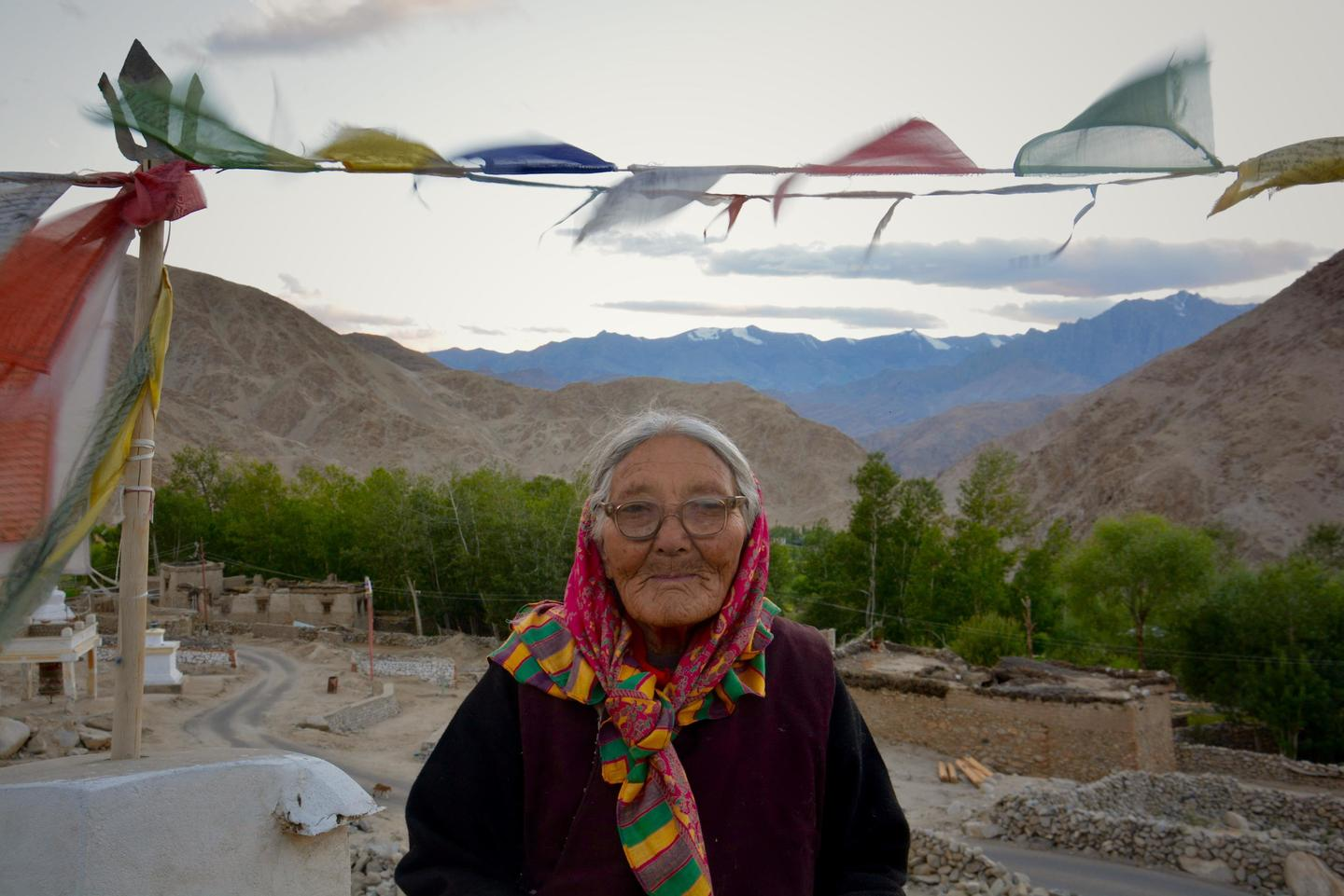 Eldery woman standing with Indian mountains in the background