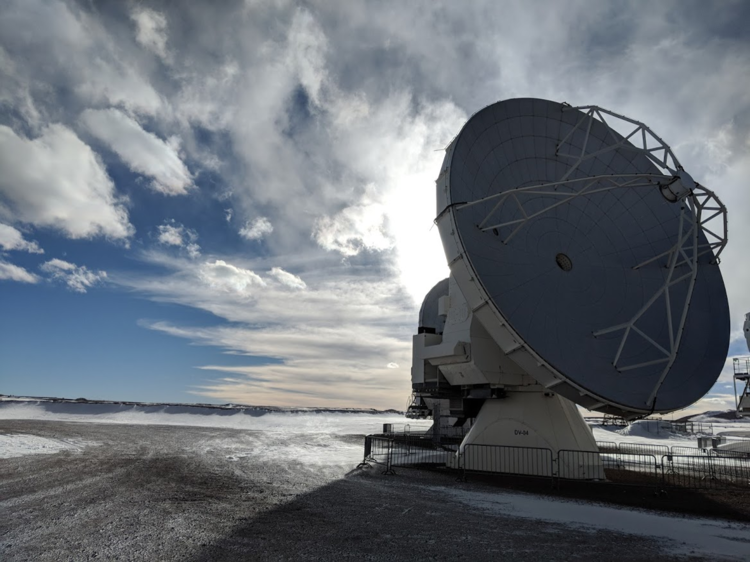 Large ground based telescope in desert with sky and clouds behind