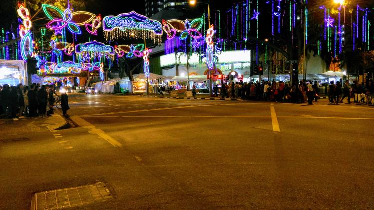 street with colorful decorative lights hanging above and people on sidewalks