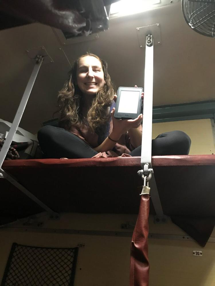 Jane in her bunk bed holding a phone